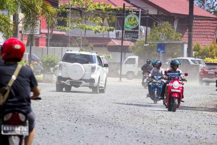 oto 2 : Pengendara yang melintas di jalan D.I. Panjaitan. Terlihat debu dan batu kerikil. Foto dok. Haning dan Rizal Alqadrie YP